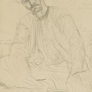 바닥에 앉아 정면을 보고 있는 터반을 두른 아랍인