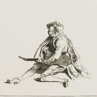 땅에 앉아 기타를 조율하는 남자