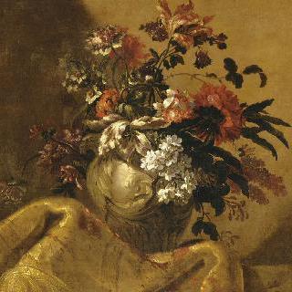 화려한 비단 양탄자 위의 흰색 대리석 화병 속의 꽃